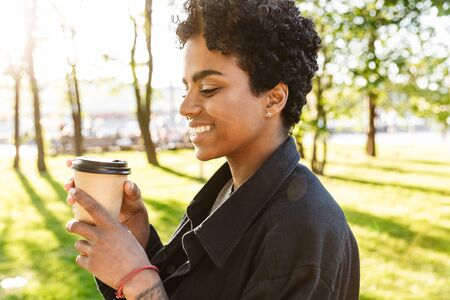 Photo of attractive african american woman with curly hair holding and drinking takeaway coffee from paper cup while walking in city park 版權商用圖片