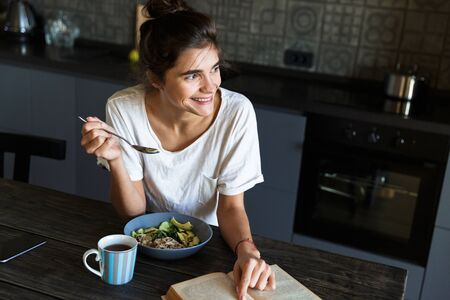 Attractive happy young woman having healthy breakfast at the kitchen at home, reading a book Stock Photo