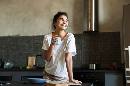 Attractive smiling young woman having healthy breakfast at the kitchen at home, holding cup Stock Photo