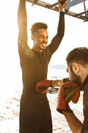 Two motivated attractive young healthy sportsmen outdoors at the beach, workout together, boxing exercises