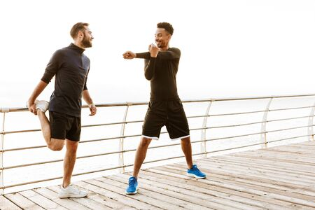 Two attractive smiling young healthy sportsmen outdoors at the beach, workout together, doing stretching exercises
