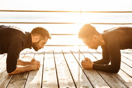 Two attractive young healthy sportsmen outdoors at the beach, workout together, plank exercise