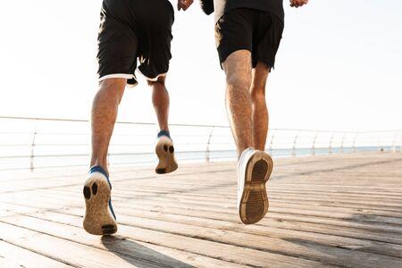 Achteraanzicht half portret van twee jonge gezonde sporters die buiten joggen op het strand Stockfoto