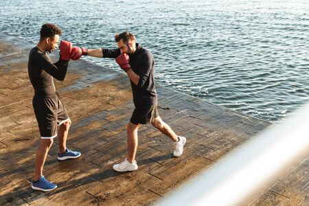 Image of concentrated handsome strong two young sports men boxers friends at the beach near sea boxing.