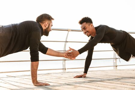 Two attractive confident young healthy sportsmen outdoors at the beach, workout together, doing push ups