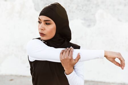 Picture of a young beautiful strong muslim sports fitness woman dressed in hijab and dark clothes posing make sport stretching exercises outdoors at the street.