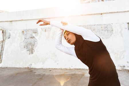 Image of a young concentrated muslim sports fitness woman dressed in hijab and dark clothes posing make sport stretching exercises outdoors at the street. Stok Fotoğraf - 128860157