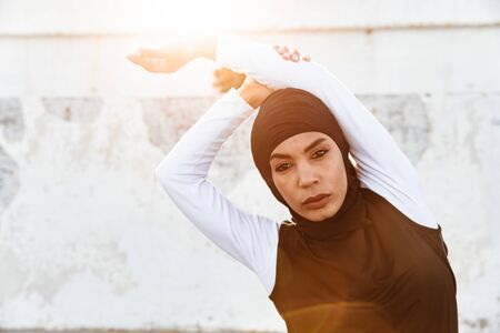 Image of a young concentrated muslim sports fitness woman dressed in hijab and dark clothes posing make sport stretching exercises outdoors at the street. Stok Fotoğraf