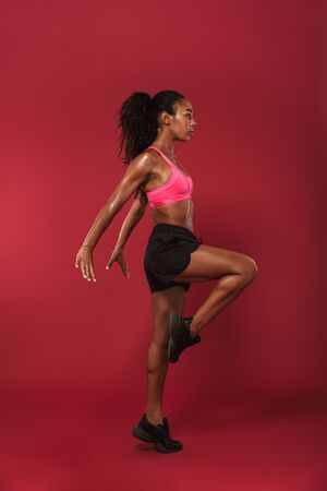 Image of a gorgeous amazing strong young african sports woman posing isolated over red wall background make sport exercises.