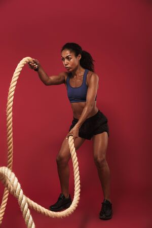 Image of a serious strong young african fitness sports woman posing isolated over red wall background make exercise for upper body with ropes.