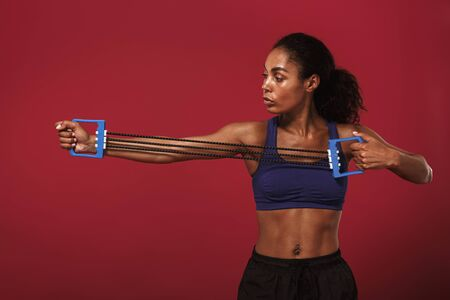Photo of a concentrated strong young african fitness sports woman posing isolated over red wall background make exercise for upper body with expander.