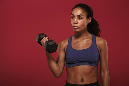 Photo of a concentrated serious strong young african fitness sports woman posing isolated over red wall background make exercise for arms with dumbbell. Stok Fotoğraf