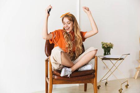Bild eines positiv optimistisch lächelnden jungen blonden Mädchens zu Hause, das Musik mit Kopfhörern hört, die auf Stuhltanzen sitzen.