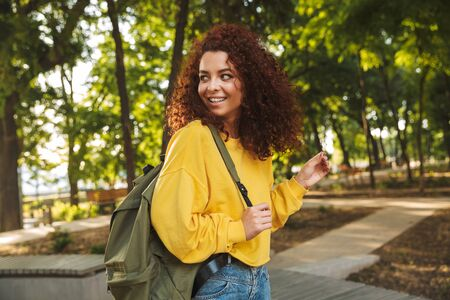 Photo of a smiling young beautiful curly student girl outdoors in nature park walking with backpack.