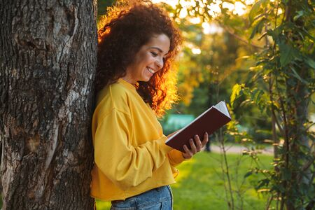 Beautiful young cheerful girl spending good time at the park, reading paper book while standing and leanig on a tree Фото со стока