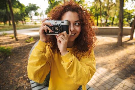 Happy young girl with red curly hair sitting on a bench at the park, taking pictures with photo camera