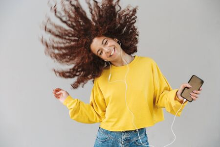 Portrait of smiling beautiful curly girl isolated over gray background using mobile phone listening music shaking hair.