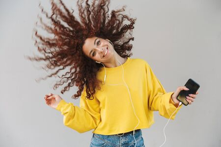 Portrait of cheerful emotional beautiful curly girl isolated over gray background using mobile phone listening music shaking hair.