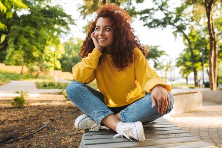 Photo of a smiling cheerful happy young beautiful curly student girl outdoors in nature park sitting on a bench.