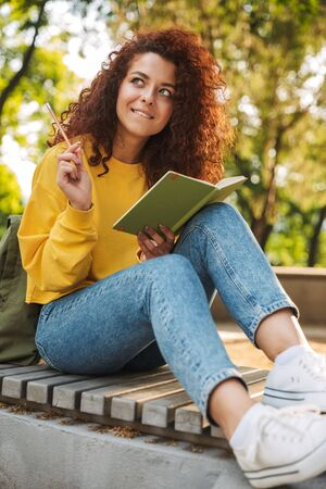 Photo of a dreaming pleased thinking young beautiful curly student girl sitting outdoors in nature park writing notes in notebook.