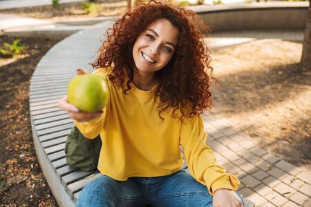 Photo of a cheerful young beautiful curly student girl outdoors in nature park sitting on a bench holing apple give it to you. Imagens