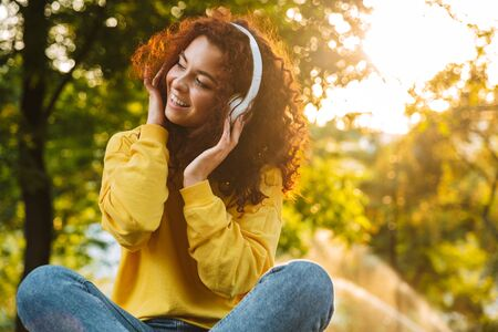 Beautiful young cheerful girl spending good time at the park, sitting on a bench, listening to music with headphones