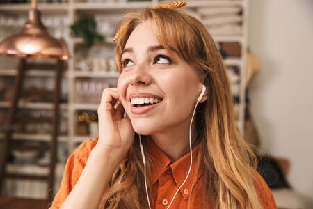 Image of a cheery young blonde girl in orange shirt at the kitchen listening music with earphones.