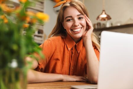 Image of a cheerful happy smiling young blonde girl at the kitchen using laptop computer.