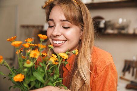 Picture of a cheery optimistic young blonde girl at the kitchen holding beautiful flowers in hands.