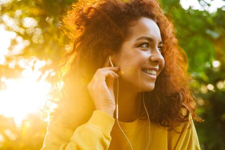 Image of a happy optimistic cute young student curly girl sitting on bench outdoors in nature park with beautiful sunlight listening music with earphones.
