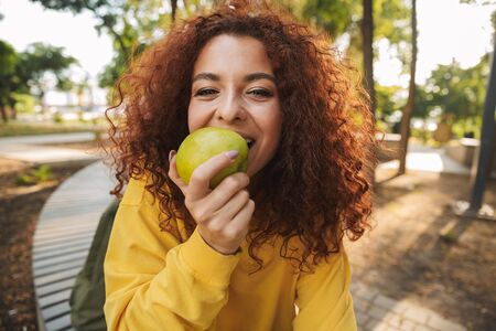 Happy young girl with red curly hair sitting on a bench at the park, biting green apple