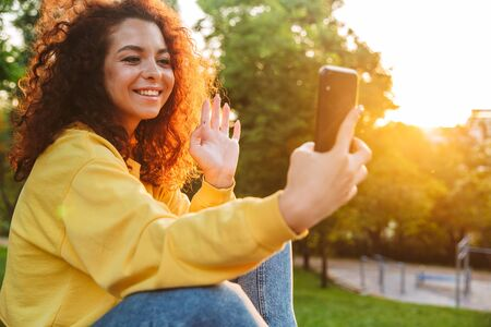 Image of a optimistic cheerful cute young student curly girl sitting on bench outdoors in nature park with beautiful sunlight using mobile phone waving talking.