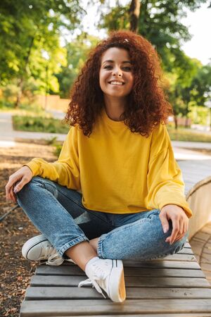 Photo of a happy young beautiful curly student girl outdoors in nature park sitting on a bench. Imagens