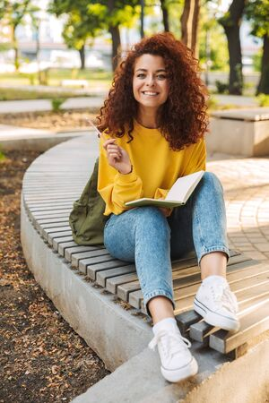 Photo of a pleased optimistic young beautiful curly student girl sitting outdoors in nature park writing notes in notebook.