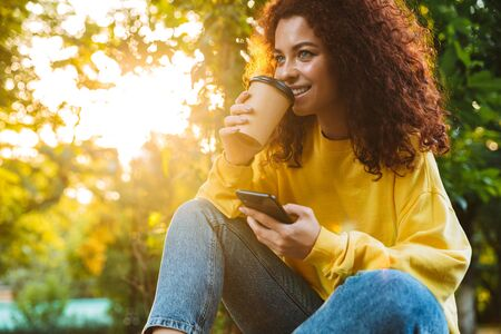 Image of a positive optimistic cute young student curly girl sitting on bench outdoors in nature park with beautiful sunlight using mobile phone drinking coffee. Фото со стока