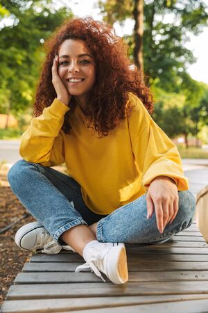 Image of a smiling young beautiful curly student girl outdoors in nature park sitting on a bench. Imagens