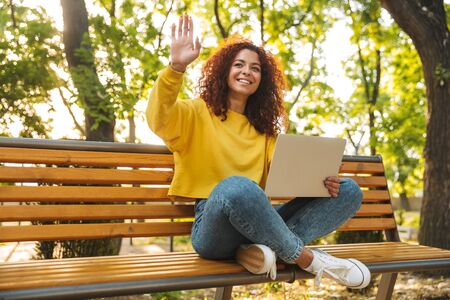 Image of a smiling cheerful young beautiful curly student girl sitting outdoors in nature park using laptop computer waving to friends.