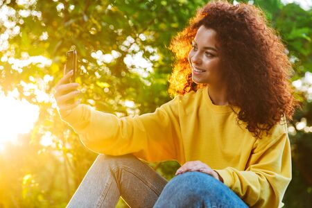 Image of joyful young woman with curly brown hair smiling and taking selfie photo on smartphone while sitting on bench in green park