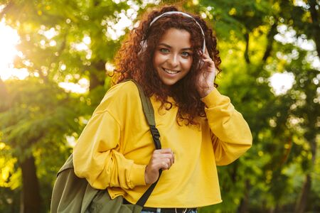 Beautiful young cheerful girl spending good time at the park, listening to music with headphones while walking Фото со стока