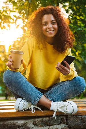 Photo of a cheerful optimistic cute young student curly girl sitting on bench outdoors in nature park with beautiful sunlight using mobile phone drinking coffee.