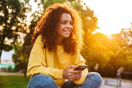 Photo d'une jeune étudiante bouclée joyeuse et joyeuse, assise sur un banc à l'extérieur dans un parc naturel avec une belle lumière du soleil à l'aide d'un téléphone portable.