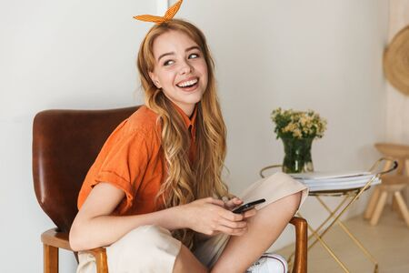 Photo of a smiling young blonde girl at home indoors using mobile phone sitting on chair.
