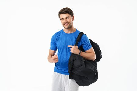 Photo of cheerful optimistic handsome young sports fitness man standing isolated over white wall background holding bag pointing to you. Stock Photo
