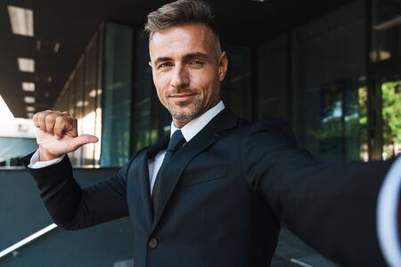 Image of a positive pleased mature grey-haired handsome business man outdoors at the street near business center take selfie by camera pointing to himself. Stock Photo