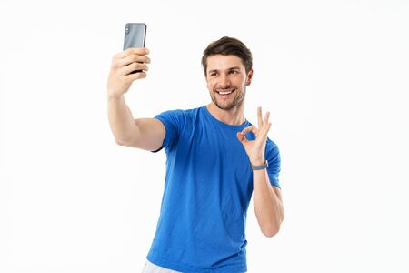 Photo of cheerful man in casual t-shirt showing ok sign and taking selfie on cellphone isolated over white background Stock Photo - 129816913