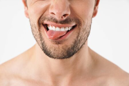 Cropped photo closeup of funny man grimacing at camera with sticking out his tongue isolated over white background