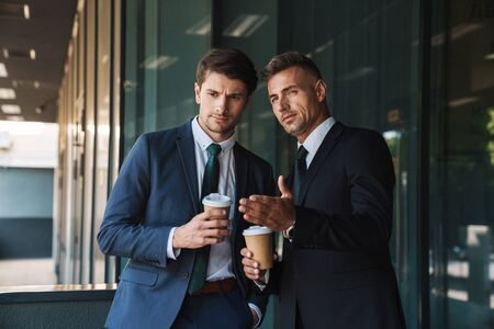 Photo of a two serious colleagues handsome business men outdoors at the street near business center talking with each other drinking coffee gossiping.