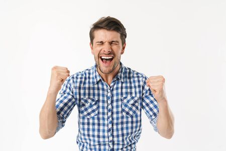 Photo of excited man in plaid shirt screaming and rejoicing with fists clenched isolated over white background