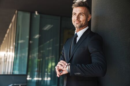 Photo of a cheerful happy mature handsome grey-haired business man outdoors at the street near business center touching watch clock. Stock Photo