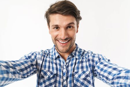 Image of a cheerful smiling young unshaved man dressed in casual shirt posing isolated over white wall background take a selfie by camera. Фото со стока - 129242416